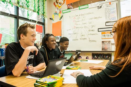 Students working on laptops at desks